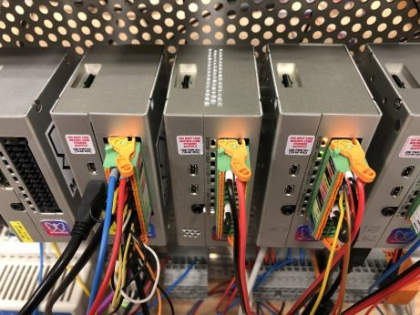 A group of Raspberry Pi 4 and Monarco HAT-based PLCs on a DIN-rail